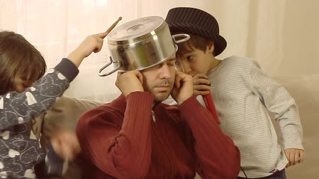 család : Busy father is trying to work on lap top, while his children are having fun, singing on a plastic microphone and drumming on a pot, successfully interrupting his concentration. Stock mozgókép