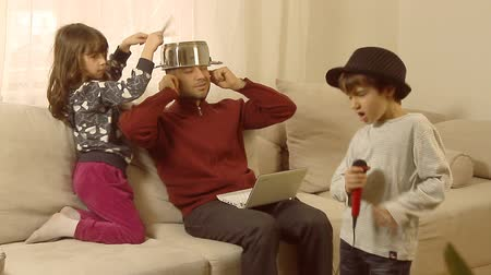 барабаны : Busy father is trying to work on lap top, while his children are having fun, singing on a plastic microphone and drumming on a pot, successfully interrupting his concentration. Стоковые видеозаписи