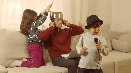 otec : Busy father is trying to work on lap top, while his children are having fun, singing on a plastic microphone and drumming on a pot, successfully interrupting his concentration. Dostupné videozáznamy
