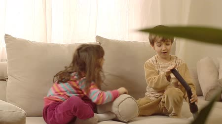 baví : Children having fun playing with vacuum cleaner, vacuuming their hair and clothes.