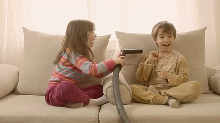 śmiech : Adorable laughing kids playing at home with vacuum cleaner.