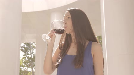 wine red : Beautiful woman in blue dress drinking red wine.