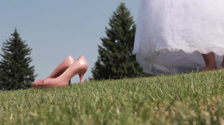 chafe : Bride takes her shoes off grass in a wedding dress
