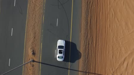 desolado : White SUV rides the desert highway. View from above.