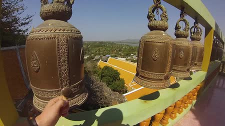 A young man strikes the bells in the temple of the Buddha in Thailand. Summer