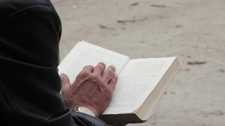 Elderly man with a book in his hands. In the frame of the book and hand Stock Footage