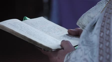 holy book : The bible is in the hands of the priest. Rite in the temple Stock Footage