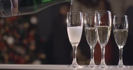 Champagne pouring into a glass, slow motion. New Years Eve, on the background of a modern Christmas tree Стоковые видеозаписи