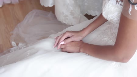 Beautiful hands of the bride on a wedding dress. Camera moves close up