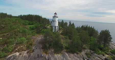 aerial motion to old lighthouse on rocky cape among lake