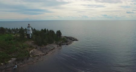 aerial flight over lighthouse on cape against huge lake