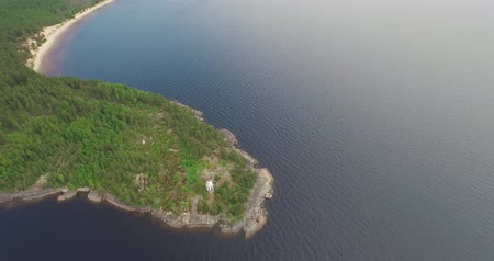 high upper flight over lighthouse on rocky cape among lake Stock Footage
