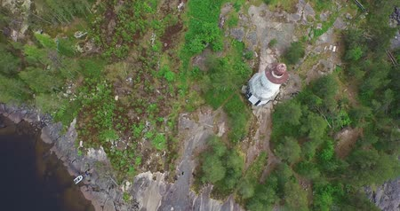 round flight over lighthouse on rocky cape to huge lake Стоковые видеозаписи