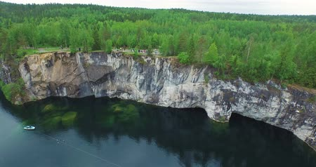 aerial forest glade on cliff with tourists lake with boat