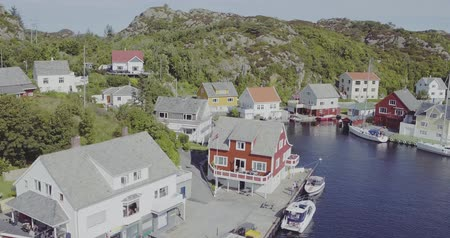 close flight over houses on fjord seafront and blue water Стоковые видеозаписи