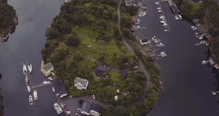 motorbot : bird eye flight over island in fjord with yachts houses road