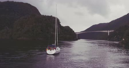 people on yacht sailing along fjord between hilly coasts
