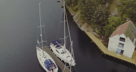 yacht shed on wooden platform yachts at pier in fjord Stock Footage