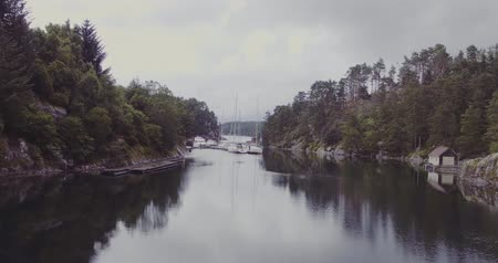motion along fjord by houses on coasts yachts on dark water Стоковые видеозаписи