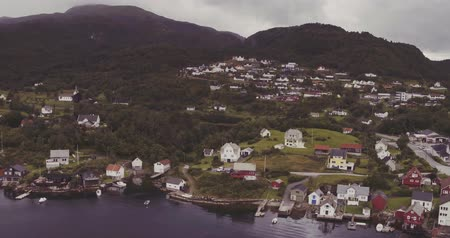 village scattered on fjord coast against green hills