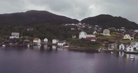small vessels : motion to village with yacht sheds on fjord coast by hills