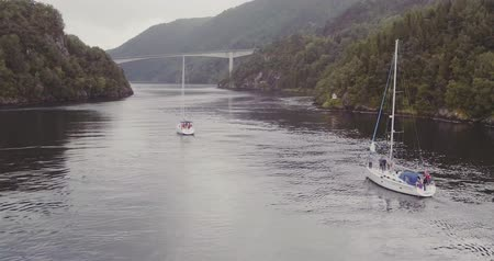 north bay : yachts sail along fjord between hilly coasts to bridge