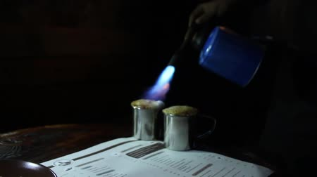 brulee : Process of caramelization of sugar on coffee creme brulee with hand held gas-burner in dark cafe.