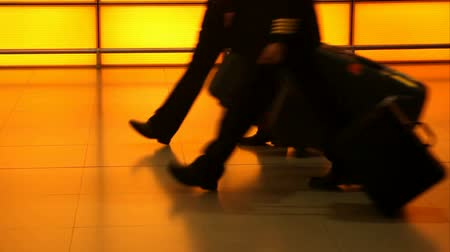 fülke : Pilot and cabin crew walking in a color tunnel in an airport silhouetted