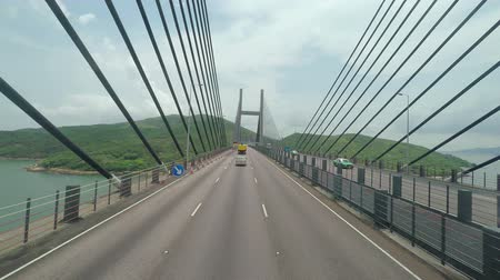 mosty : Hong Kong, China - June 12, 2015: Driving along the suspension bridges that are part of the highway connecting the Hong Kong International airport to the city centre