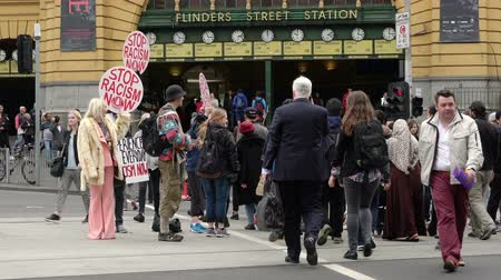 смещение : Melbourne, Australia - Sep 18, 2015: 4k video of protesters holding stop racism now placards in the crowd outside Flinders Street Station in Melbourne, Australia Стоковые видеозаписи