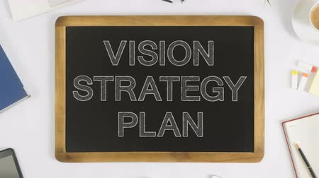 vizyon : 4k video of writing the words vision, strategy and plan words on a chalkboard at office desk