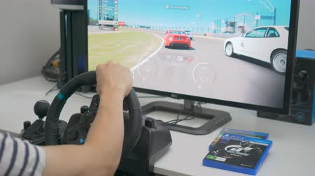 playstation : Melbourne, Australia - Jan 30, 2018: A man playing Gran Turismo Sport on PlayStation 4 Pro with steering wheel at home. GT Sport is a popular racing game developed by Polyphony Digital.