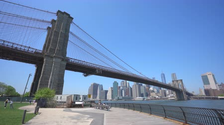 modern gebouw : New York, Verenigde Staten - 8 mei 2018: Bewegende schot van skyline van Manhattan en Brooklyn Bridge overdag Stockvideo