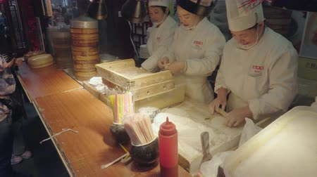 bamboo basket : Shanghai, China - Nov 5, 2017: 4k video of Chefs making Shanghai dumplings, also called xiaolongbao, for sale at a food stall. It is a type of popular traditional food in China.