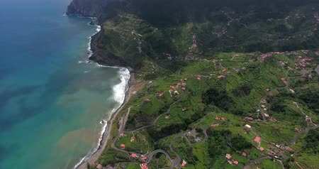 vulkán : Remote village with houses on the green hills by the sea, aerial view, Madeira, Portugal .