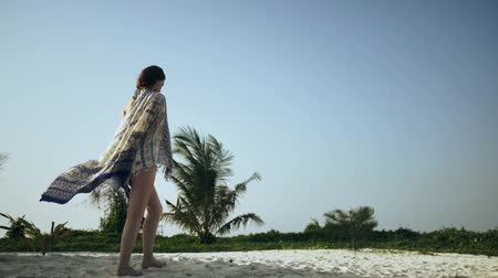 Beautiful girl is walking along the beach in a pareo