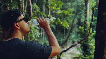 Man in the purchase of drinking water in a hot tropical forest Dostupné videozáznamy