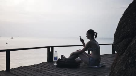 Girl on the beach with a smartphone on a trip