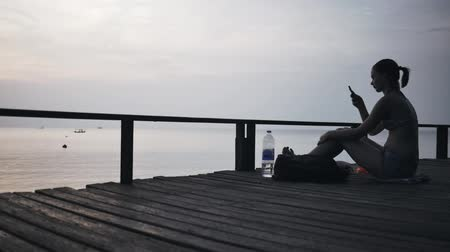 Girl on a jetty with a smartphone on a trip