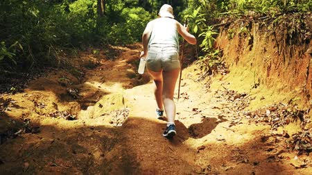 The girl is walking heavily on a mountain trail Wideo