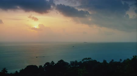 Sunset on the sea in the rainforest from a height. timelapse