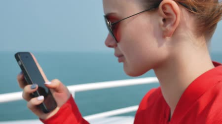 бортовой : Cute gorl using mobile phone on travel vacation at ocean.
