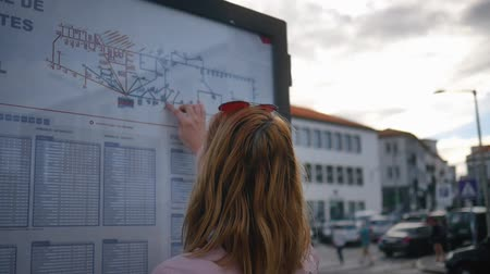 Tourist looks at the bus schedule on the street Dostupné videozáznamy