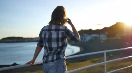 çeşnili : Girl in a shirt walks along the waterfront Stok Video
