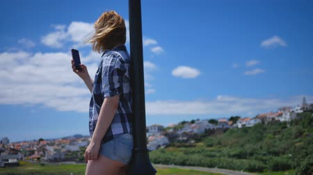 Girl in short shorts stands on the dock with the phone