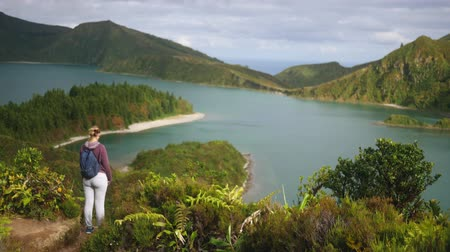 young girl tourist stands near a mountain lake at a height overlooking the ocean Dostupné videozáznamy