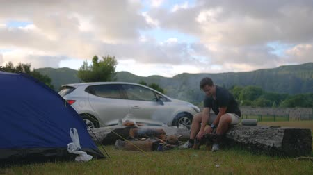 camping in nature with a fire and a guy playing with a dog on the background of a landscape and car