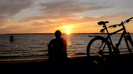 river ocean : Man and Bicycle on the coast at sunset   Stock Footage