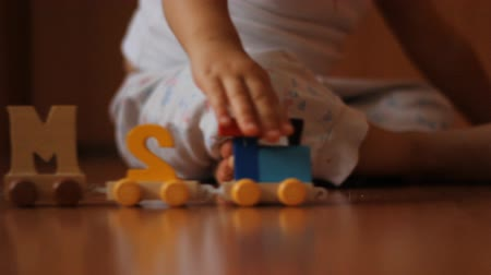 одиноко : A child dressed in white playing with wooden toys on the floor