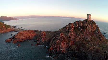 takeoff area : Flight and takeoff over old tower with background of the sea and islands at sunset. Tour de la Parata, Ajaccio, Corsica, France. Aerial panoramic view. Stock Footage